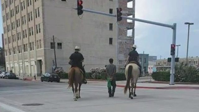 Mounted officers use rope to lead handcuffed man along Texas street