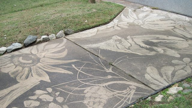 Woman creates beautiful art on driveway with power washer